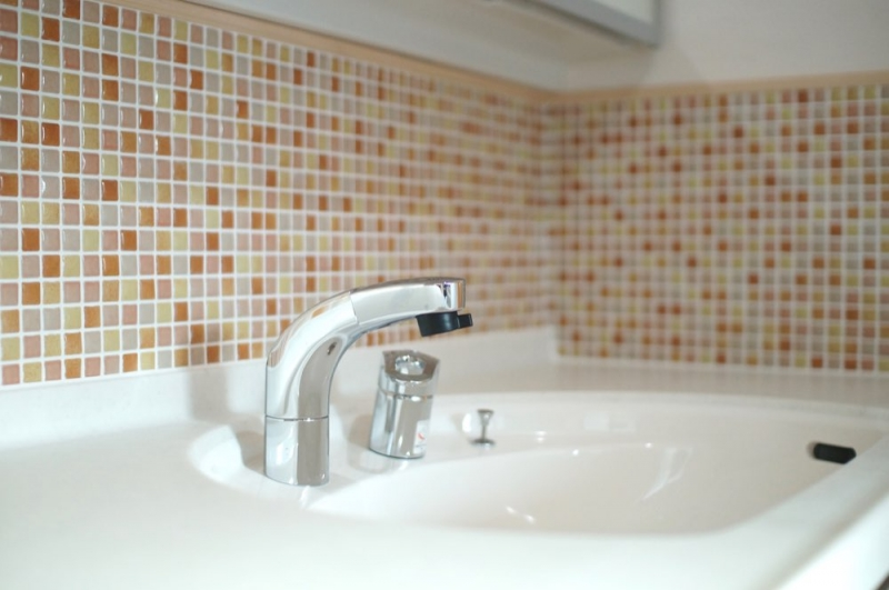 <p>洗面室の壁は漆喰。化粧台の立ち上がり壁はかわいらしいモザイクタイルでアクセントを。</p>