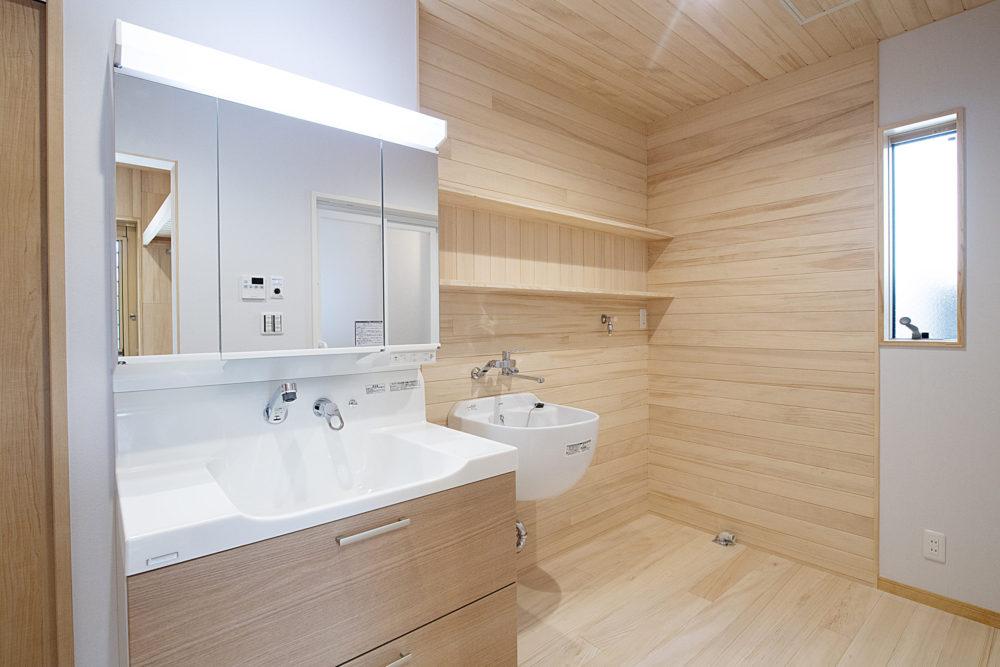 <p>1階サニタリーは介助がしやすいように広くしています。 洗濯機横には多目的に使えるシンクを設置しました。 上部の棚は日々使う洗剤やタオル等を置くことができます。 樅の木の内装材なので、湿気を吸います。調湿効果で結露やカビを防ぎます。</p>